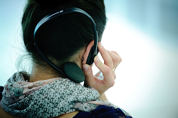 Woman listening with headphones (photo from Wikimedia Commons)
