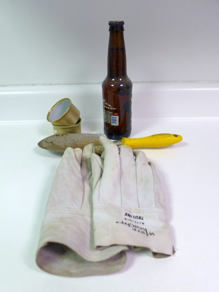 Slugfest tools: beer, small catfood cans, trowel, garden gloves (photo by Kate St. John)